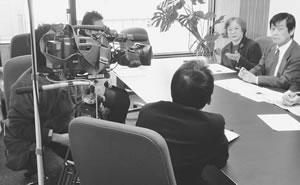 テレビ局のインタビューをうける関理事長ら