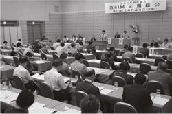 第61回定期総会で総括方針案を提案する関理事長